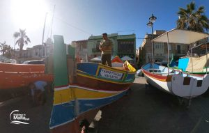 The traditional Maltese boat Luzzu on land with a man doing maintenance on it in Marsaxlokk